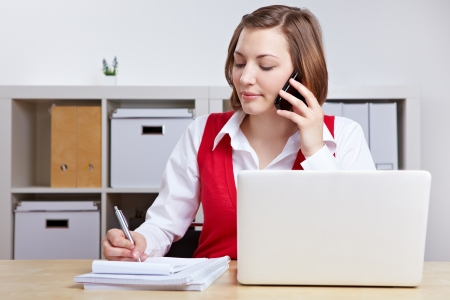 calling on phone: Woman working at desk with laptop computer and mobile phone Stock Photo