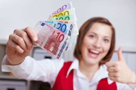 money euro: Happy woman in office with Euro money fan holding her thumbs up
