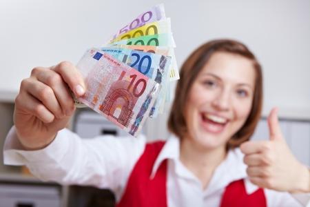 dinero euros: Mujer feliz en oficina con el ventilador del dinero Euro sosteniendo sus pulgares para arriba