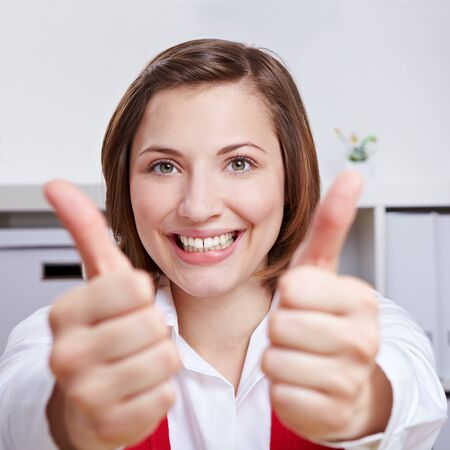 Happy business woman cheering with her two thumbs up in the office photo