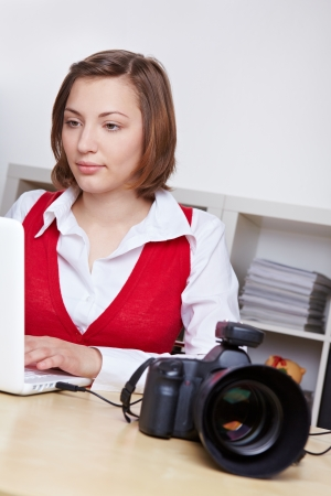 Professional female photographer transfering images from DSLR camera to laptop computer photo