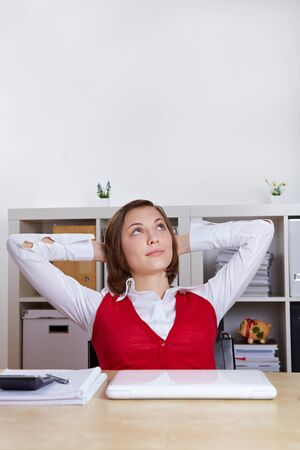 Relaxed woman sitting at her desk and looking up pensively photo