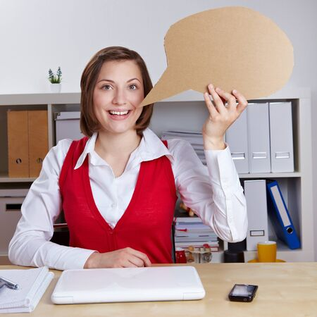 employee satisfaction: Business woman holding empty speech balloon in her office