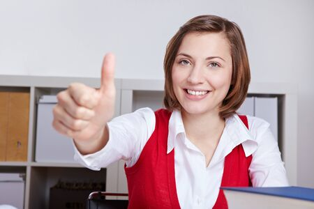 Happy woman in business office holding thumbs up photo