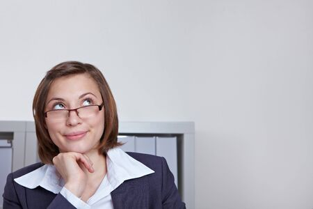 guess: Attractive business woman in office looking pensively up Stock Photo