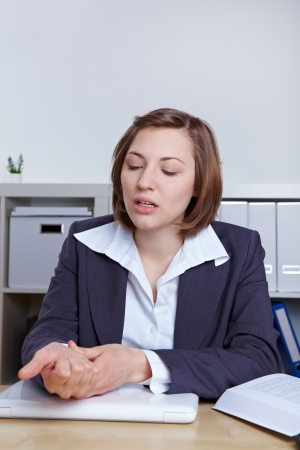 wrist pain: Business woman sitting with wrist pain at her desk in the office Stock Photo