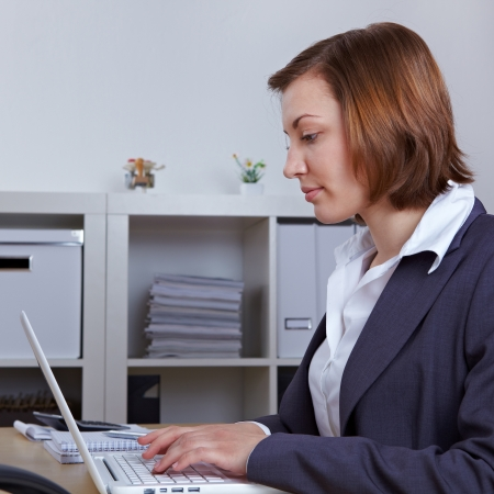 Attractive businesswoman typing on laptop computer in the office photo