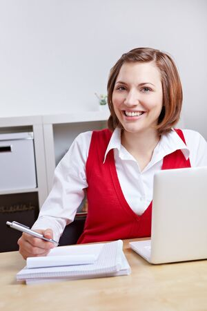 Happy smiling female student at desk with laptop computer learning Stock Photo - 14154714