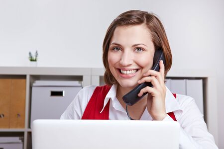 Happy woman in office calling the customer support hotline photo