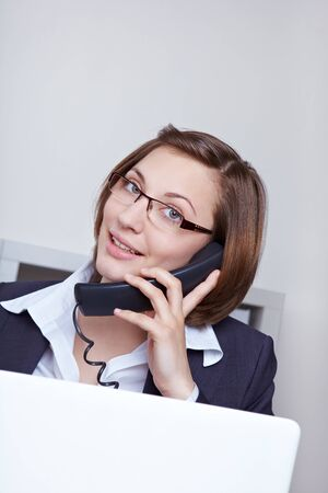Business woman with laptop computer in office calling customer support hotline photo