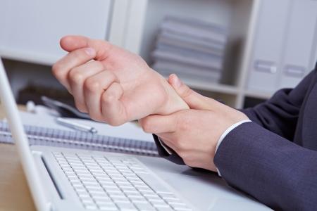 dolor muscular: Manos con síndrome RSI sobre el teclado de la computadora portátil