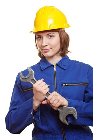 Female builder in overall with helmet and big wrench photo