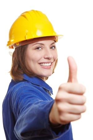 man's thumb: Happy female worker in blue overall and hardhat holding thumbs up