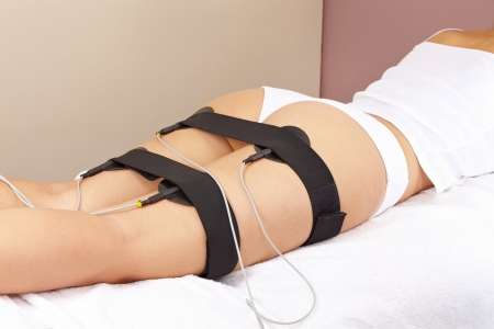 electric current: Woman getting electric massage for leg muscles in spa