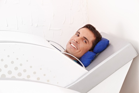 Man lying smiling in cabin ozone in spa photo