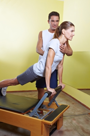 posture correction: Trainer helping woman with posture correction in fitness center