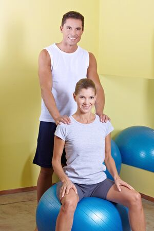 Happy man and woman in fitness center with gym ball photo