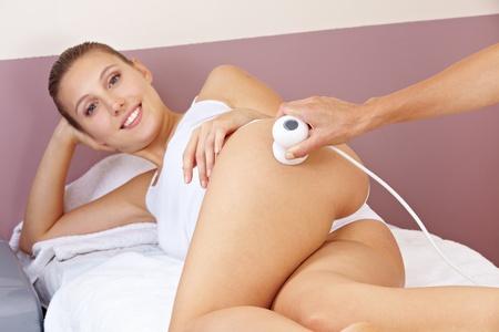 nalga: Mujer recibiendo estiramiento de la piel mediante la estimulación eléctrica en el spa