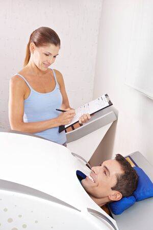 Happy man in cabin ozone for skin treatment with fitness trainer in spa photo