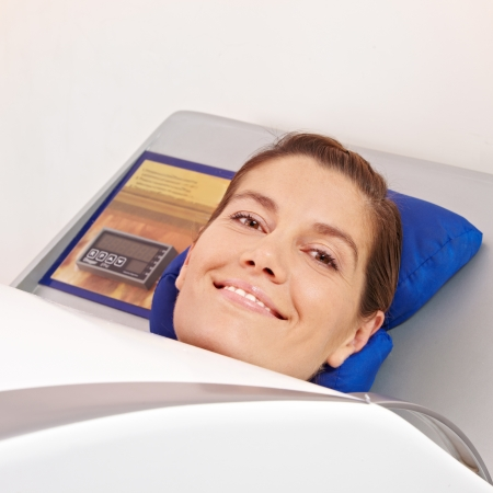 Smiling woman laying in cabin ozone for skin treatment in spa photo