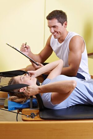 Woman and male trainer talking in fitness center while exercising photo