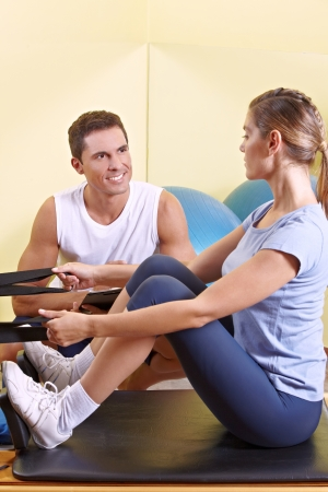 Attractive woman exercising in fitness center and talking to male fitness trainer photo