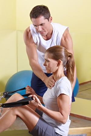 Trainer giving advice to woman in fitness centerat rowing machine photo