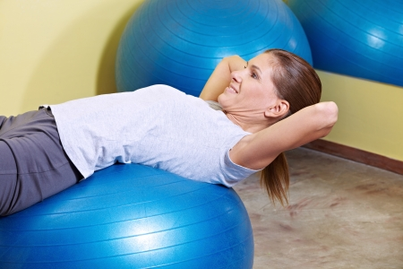 fit ball: Woman doing sit-ups on gym ball in fitness center Stock Photo