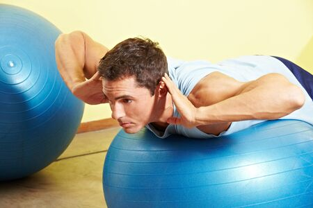 back exercise: Man exercising his back on gym ball in fitness center