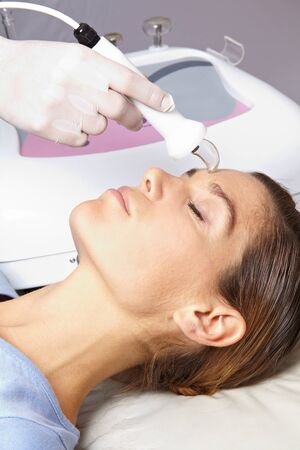 High frequency skin treatment in female face in spa Stock Photo