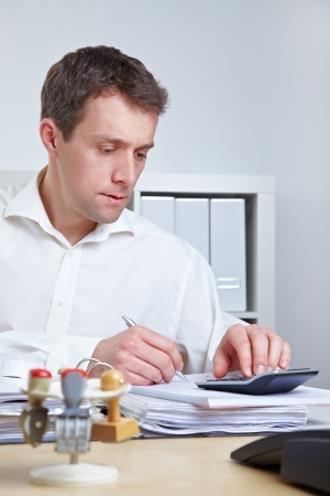 Business man at his desk using a calculator in the office Stock Photo - 14249632