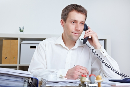 Business man making a call at his desk in the office Stock Photo - 14249629