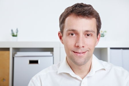 merchant: Portrait of a smiling business man sitting in the office