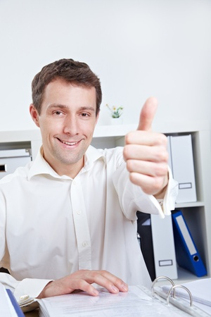 Smiling business manager holding his thumb up in the office Stock Photo - 14249624