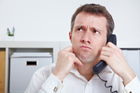 Frustrated business man on the phone in waiting queue Stock Photo - 14249637