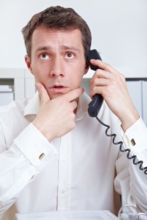speculate: Business man at desk in office thinking on phone