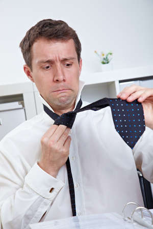 Business man uncertain looking at tie in his office photo