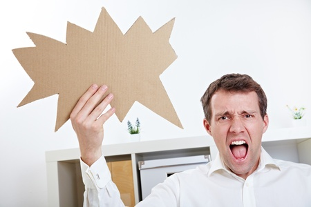 controversy: Angry man screaming with speech balloon in his office Stock Photo