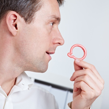 Business man holding speech balloon symbol near his mouth photo