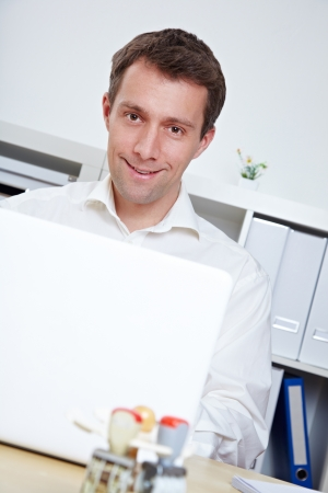 electronically: Smiling business man at desk with laptop in the office
