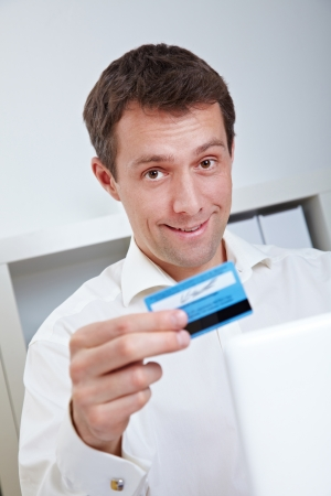 electronically: Smiling business man with laptop and credit card in office