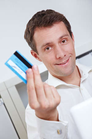ec: Business man on laptop showing credit card in his office Stock Photo