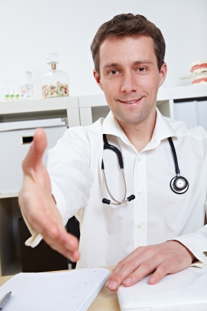 Physician at his desk offering hand for handshake in his office photo