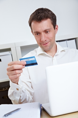 electronically: Business man buying online with credit card and laptop