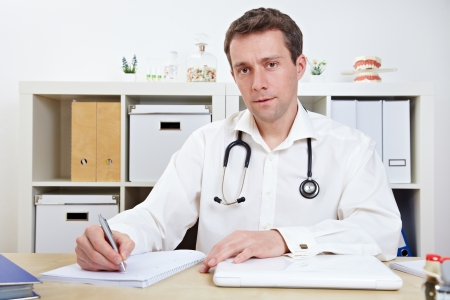 Doctor taking notes in office during a consulation photo