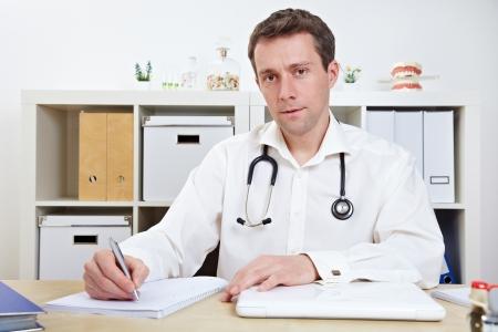 taking note: Dottore prendere appunti in carica durante un consulto Archivio Fotografico