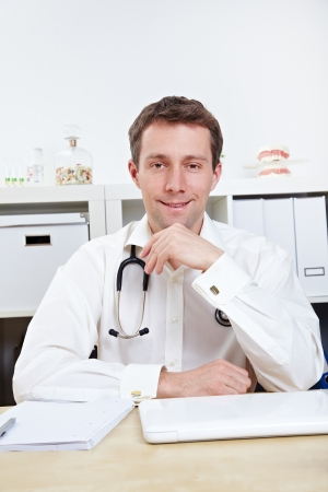 Smiling doctor in office listening to a patient photo