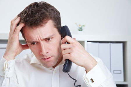 to queue: Frustrated business man waiting on the phone in a hotline queue
