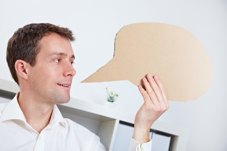 dialog balloon: Manager holding comic speech balloon near his mouth in office