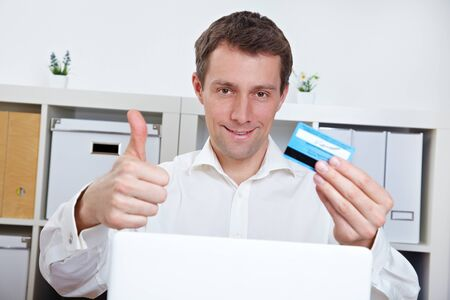 Happy business man with credit card holding thumbs up in the office photo